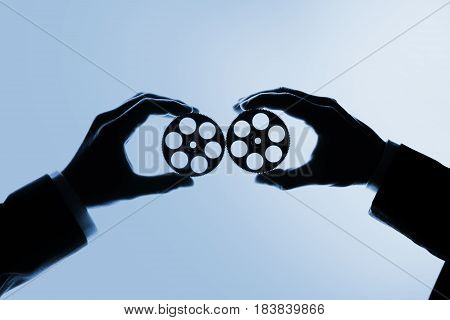 Two people's hands holding gears - working together concept