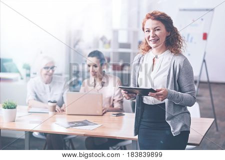 Best team. Positive delighted red-haired woman keeping smile on her face standing on the foreground while looking straight on camera