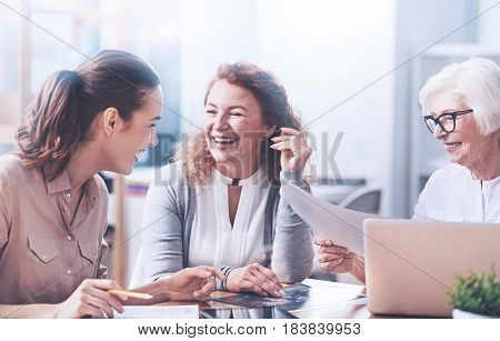 Listen to me. Three positive colleagues smiling while looking at each other, holding hands on the table