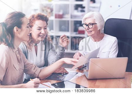 At the meeting. Three delighted female workers looking at the document gesticulating while working together