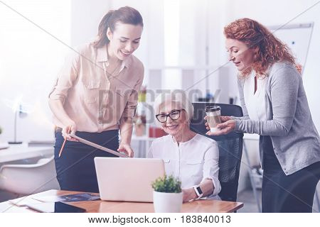 Work with pleasure. Positive delighted old businesswoman putting hands on the table, looking at her laptop sitting on black chair between two assistants