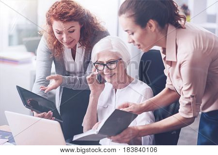 Give it to me. Smiling elderly female holding phone near right ear looking into notebook that her secretary show