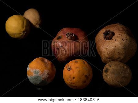 Punch of mouldy unhealthy fruits including pomegranate lemons and oranges