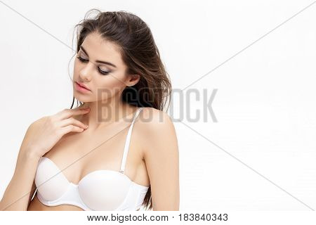 portrait of young beautiful woman brunette with natural makeup in the white lingerie