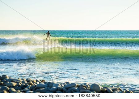 Surfing in the spring. Clear lite waves and surfer in ocean