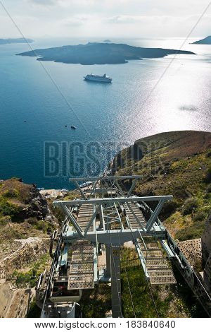 Volcano island with cruisers anchored around, a view from ropeway above port of Fira at Santorini, Greece