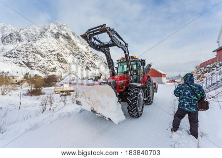 The man by the side of the road bypasses a snow-plow tractor in the snow-covered fishing village of Lofotens