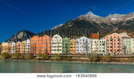 Innsbruck - November of 2014, Austria: Сolored houses on the bank of the river Inn, Innsbruck cityscape in sunny day with mountains and clear blue sky