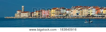 Piran - November of 2014, Slovenia: Panorama of the old town of Piran, two fishermen in the boat, Adriatic sea
