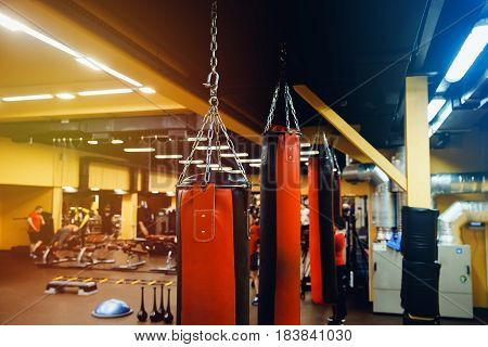 Punching bag in the gym. Against the backdrop of athletes. Gym is a cellar. Pear for boxing.