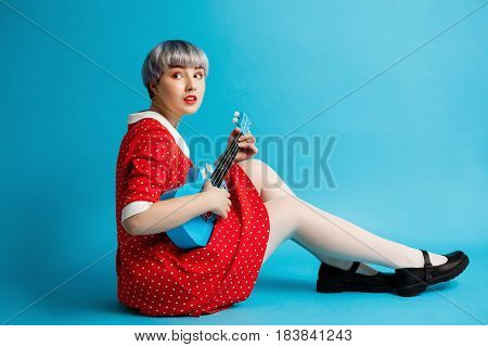 Close up portrait of beautiful dollish girl with short light violet hair wearing red dress holding ukulele over blue background. Copy space.