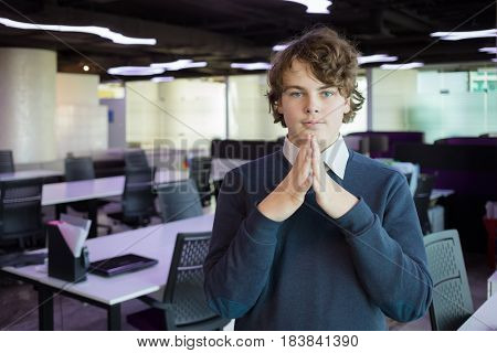 Handsome teenager poses with folded hands in modern office with many workplaces