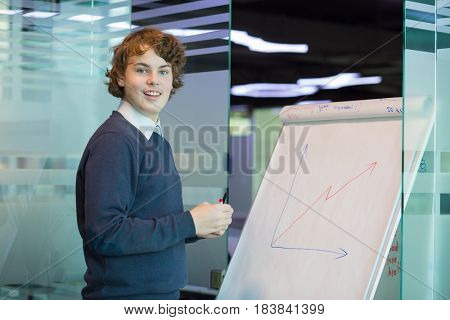 Handsome smiling teenager draws graph on paper in modern office