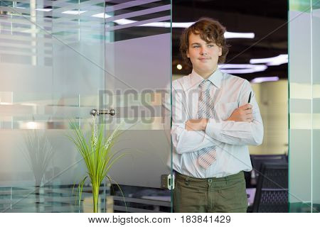 Smiling teenager in shirt and tie poses near glass door in modern office