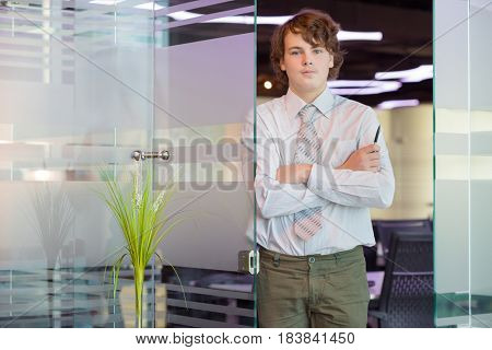 Handsome teenager in shirt and tie poses near glass door in modern office