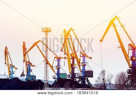 MURMANSK, RUSSIA- APRIL 2, 2017: Embankment along with the river port, the crane unloads coal. high contrast and monochrome color tone.