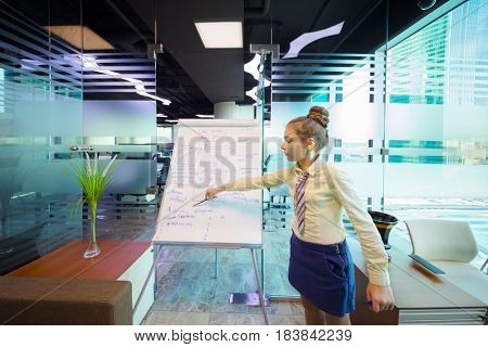 Girl shows her project on paper in office, Text translation - new building in Moscow, child dream, pool with slides, kindergarten, brick building, glass windows
