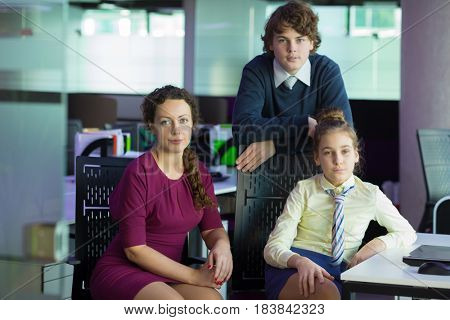 Woman, girl, boy pose near table in modern office, focus on woman