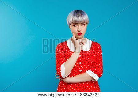 Close up portrait beautiful dollish girl with short light violet hair wearing red dress over blue background. Copy space.