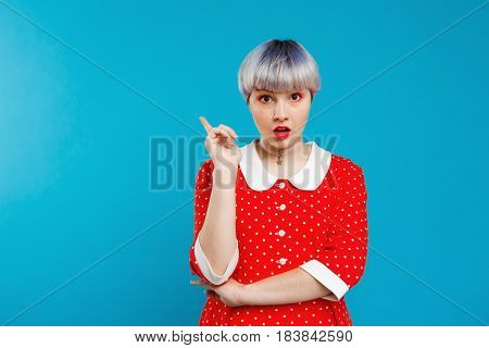 Close up portrait upset beautiful dollish girl with short light violet hair wearing red dress over blue background. Copy space.