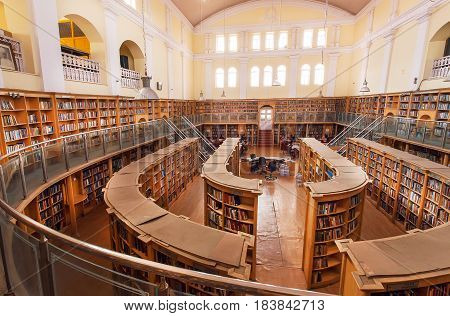 BANGALORE, INDIA - FEB 12, 2017: Wide hall of the Karnataka State Central Library Street with old wooden bookshelves on February 12, 2017. Established in 1915 and housed with 2.500.000 books and rare volumes