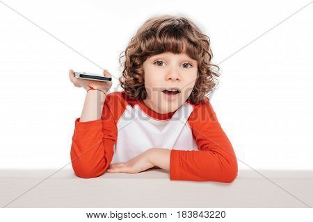 Curly little boy holding smartphone in hand