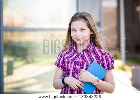 Ten Years Old Blue Eyed Schoolgirl Holding A Book