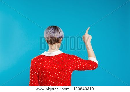 Close up portrait from back beautiful dollish girl with short light violet hair wearing red dress pointing with finger over blue background. Copy space.