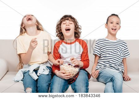 Cheerful group of friends sitting on couch with popcorn and have fun