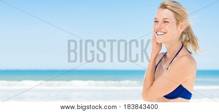 Smiling fresh woman sunbathing at beach. Happy woman refreshing herself at tropical  beach. Blonde girl with toothy smile with blue bikini at seaside.