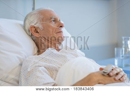 Sad senior man lying on hospital bed and looking away. Old patient with oxygen tube feeling lonely and thinking at hospital. Sick aged man lying hospitalized in a medical clinic.