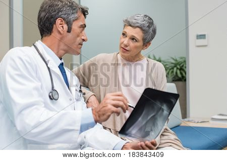 Male doctor and senior patient discussing scan results at the office. Doctor showing to senior woman x-ray in a medical clinic. Mature doctor showing a radiography to his patient.