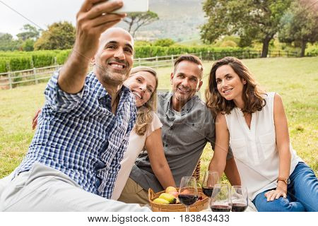 Group of four mature friends taking selfie photo at picnic. Happy middle aged couples looking into camera phone while man taking photo. Happy men and smiling women posing for selfie at park.