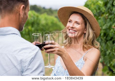 Couple of winegrowers drinking wine in vineyard. Close up face of happy smiling woman with straw hat toasting whit her husband. Mature couple tasting wine in vineyard.