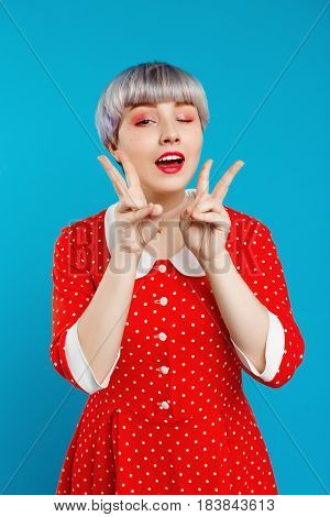 Close up portrait beautiful dollish girl with short light violet hair wearing red dresswinking showing victory gesture  over blue background. Copy space.