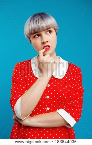 Close up portrait thoughtful beautiful dollish girl with short light violet hair wearing red dress over blue background. Copy space.