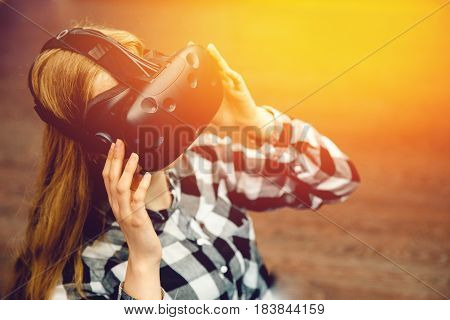 Blonde girl in glasses and mask for BP. Corrects glasses. With a sunlight and toning. The concept of virtual reality.high contrast.view from above