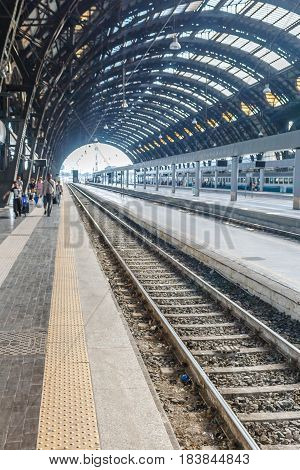 Conceptual image of european railway station and Commuters on platform in Italy