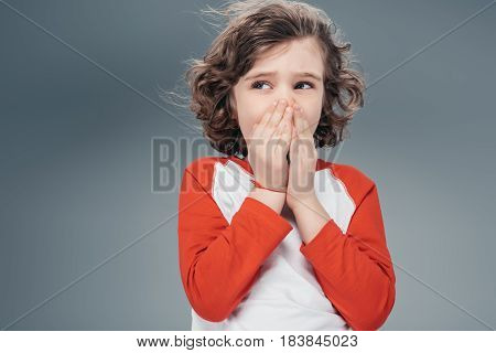 Surprised curly boy covering face by hands isolated on gray