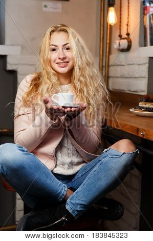 Happy girl with cup of coffee in cafe