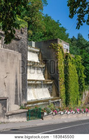 Beautiful modern wall fountain with flowers around at a hot sunny summer day in Lyon, France