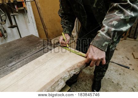 Pencil in the carpenter's hand. Carpenter measures the width of the board with a tape measure in the workplace