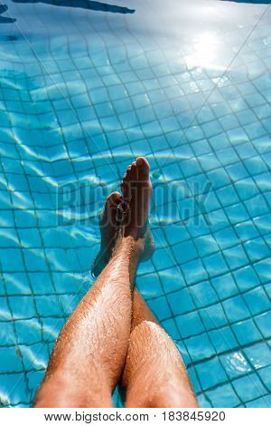 Girl lies in pool with clear blue water