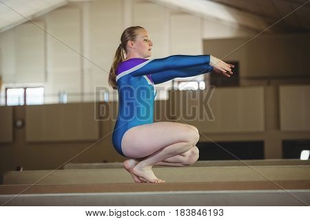 Female gymnast practicing gymnastics on the balance beam in the gymnasium