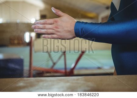 Mid-section of a female gymnast rubbing her hands with chalk powder