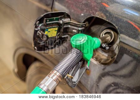 Close-up of fuel nozzle refilling the car at filling station