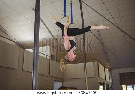 Female gymnast practicing gymnastics on rings in gymnasium