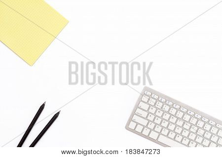 Yellow Legal Pad, Two Black Pencil And Keyboard On A White Background. Flat Lay. Top View.
