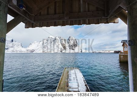 Wooden floating pier in the arch against the background of snowy Lofoten mountains