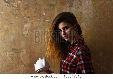 Teatime and ceremony. Pretty girl or beautiful woman with stylish blond long hair in red plaid shirt holding white ceramic tea pot teapot on beige wall